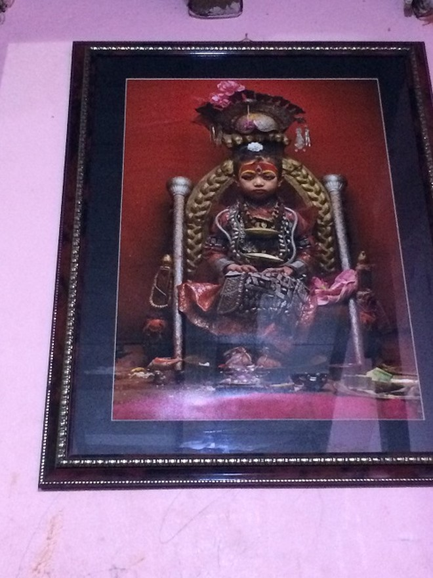 Bức ảnh nữ thần Kumari được treo trang trọng trên tường ngôi nhà mà cô bé đang ở