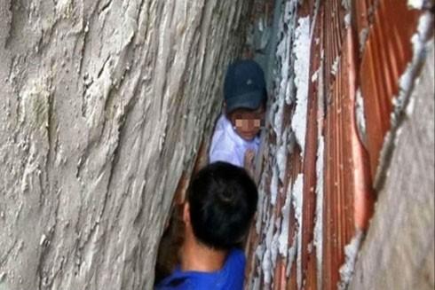 Giải cứu bé trai mắc kẹt giữa 2 bức tường nhà người dân. Ảnh: Thanh Niên