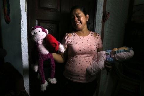 Bà nội của bé Valeria cầm trên tay những món đồ chơi yêu thích của cô bé xấu số