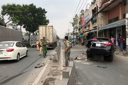 Công an xử lí hiện trường sau vụ va chạm giữa xe ô tô và xe container (Theo Tuổi trẻ)
