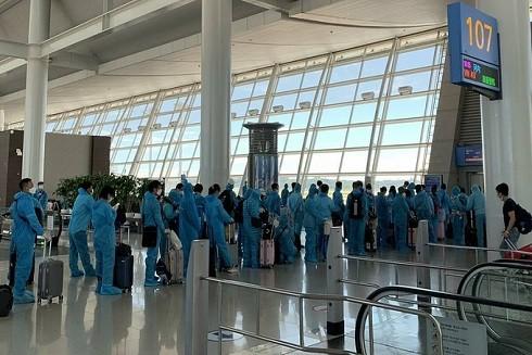 Công dân Việt Nam mặc đồ bảo hộ, xếp hàng tại sân bay ở Hàn Quốc, chờ lên chuyến bay về nước, ngày 26-7. Ảnh: Bộ Ngoại giao.