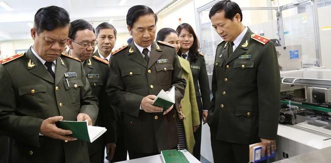 Thứ trưởng Thường trực Đặng Văn Hiếu với cuốn hộ chiếu sản xuất từ dây chuyền mới