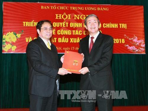 Đồng chí Đinh Thế Huynh, Ủy viên Bộ Chính trị, Thường trực Ban Bí thư (bên phải) trao Quyết định của Bộ Chính trị cho đồng chí Phạm Minh Chính