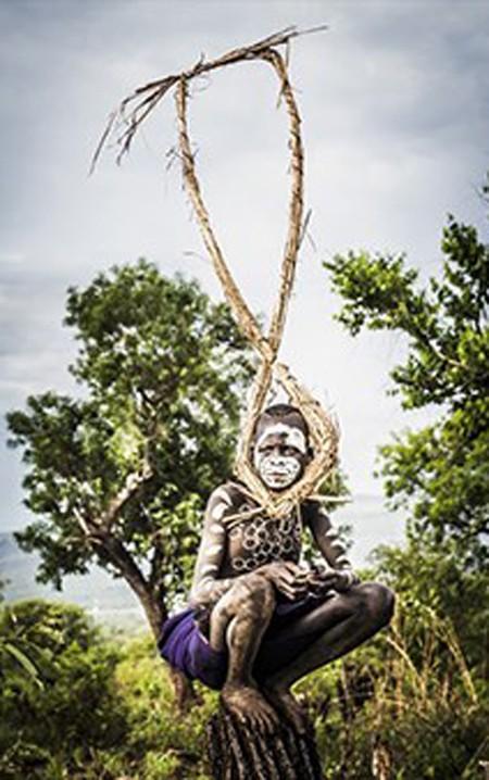 Seton phải mất ba ngày lái xe từ Addis Ababa để đến chụp ảnh bộ lạc Suri, cư trú tại làng Naregeer trong thung lũng Omo Rover - một khu vực xa xôi của Ethiopia, gần biên giới của Nam Sudan. Đây là bức ảnh đầu tiên trong ngày, bấm máy vào lúc 6h00, cậu bé bộ lạc Suri ngồi trên một thân cây khô giữa cánh đồng lúa miến.