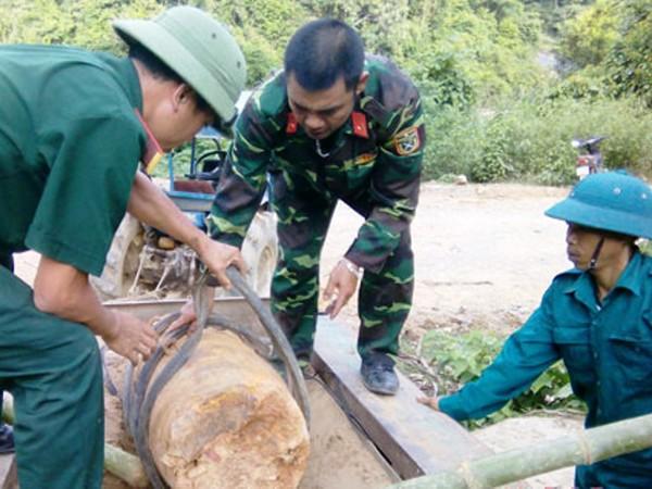 Lực lượng chức năng di dời quả bom ra khỏi khu dân cư để phá hủy một cách an toàn (ảnh: T.H)