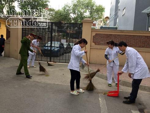 Công an quận Hoàn Kiếm và cán bộ viên chức Bệnh viện Việt Đức quét dọn vệ sinh quanh khu vực bệnh viện.