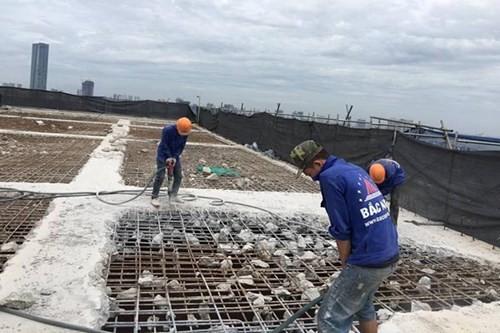 Công nhân tiến hành khoan, phá dỡ phần công trình xây dựng trái phép ở toà nhà số 8B Lê Trưc