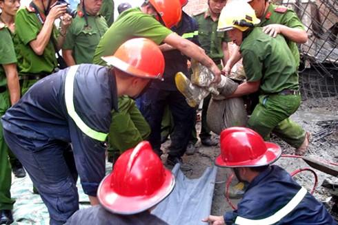 Sau một giờ cắt bêtông và sắt thép, cảnh sát cứu hộ đưa nạn nhân bị vùi lấp ra ngoài