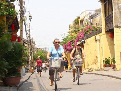 Du khách nước ngoài thong thả đạp xe dạo quanh phố cổ Hội An