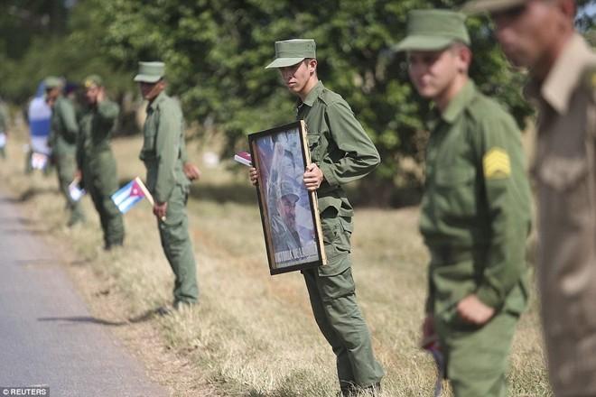 Các binh sĩ cầm di ảnh lãnh tụ Fidel chờ ở bên ngoài thủ đô Havana để đón đoàn xe. Rời thủ đô, tro cốt của ông Fidel sẽ được đưa đi dọc các vùng quê của Cuba. Ảnh: Reuters.