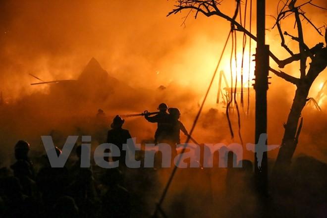 Các hộ dân trong làng Trung Văn hốt hoảng khi phát hiện hàng ngàn mét vuông xưởng nhựa ở cuối làng đang chìm trong biển lửa. (Ảnh: Minh Sơn/Vietnam+)