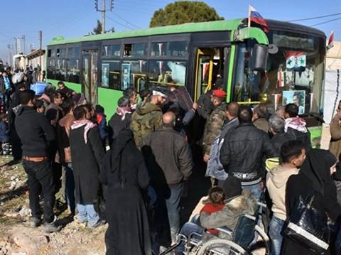 Người dân Aleppo lên xe buýt của quân chính phủ, rời khỏi khu vực chiến sự, ngày 9-12-2016