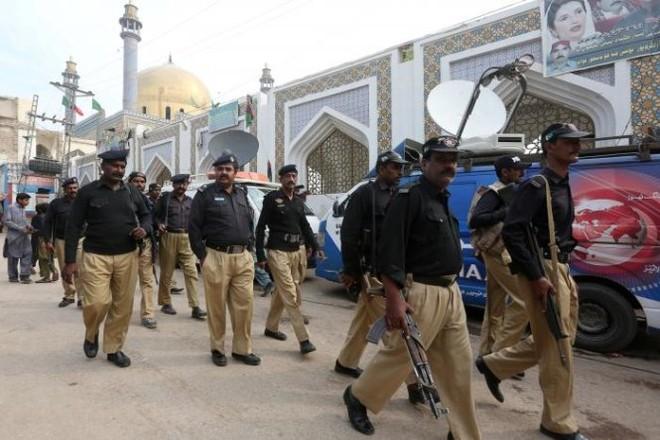 Cảnh sát Pakistan tập trung bên ngoài đền Lal Shahbaz Qalandar hôm 17-2, một ngày sau vụ đánh bom làm 83 người chết - Ảnh: Reuters
