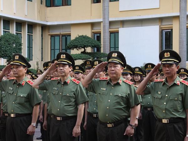 Thứ trưởng Bùi Văn Thành (hàng đầu, thứ hai từ phải sang) và các cán bộ, chiến sĩ thực hiện nghi lễ chào cờ trong trang phục mới.