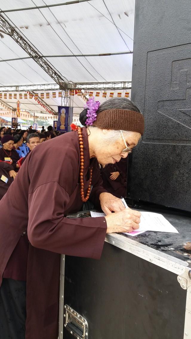 Cụ Nguyễn Thị Ty, 75 tuổi, ở TP Uông Bí đang ghi tên người thân bị TNGT vào danh sách để cầu siêu chân linh