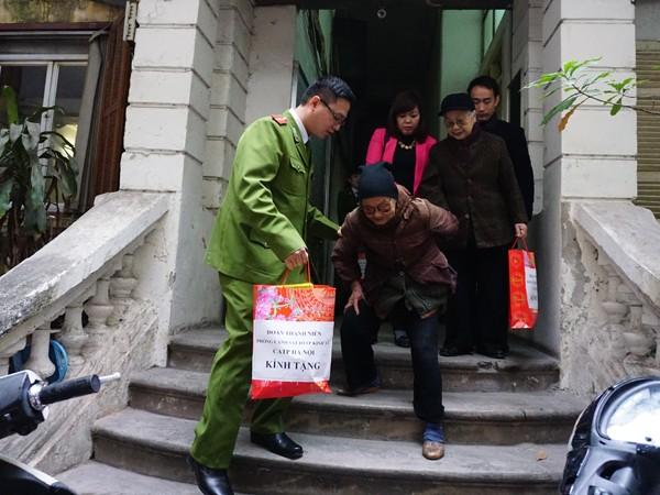 Cán bộ CAP Hàng Bài giúp đỡ cụ Trương Thị Hoa, 85 tuổi, trú tại số 4 Ngô Thì Nhậm, gia đình có hoàn cảnh khó khăn đến nhận quà