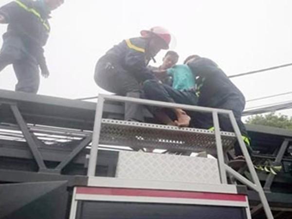 Lực lượng cứu nạn dùng xe thang đưa người đàn ông từ trên cây xuống đất
