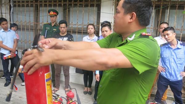 Cán bộ Cảnh sát PCCC số 2 hướng dẫn người dân sử dụng bình chữa cháy xách tay để dập cháy gas