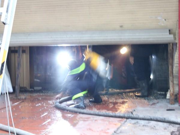Lực lượng cứu hỏa phá cửa cuốn để tiếp cận hiện trường dập lửa
