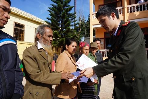 Đại úy Vũ Mạnh Hùng, Phó Tổng biên tập Báo ANTĐ trao tặng quà Tết cho đồng bào nghèo xã Hướng Phùng