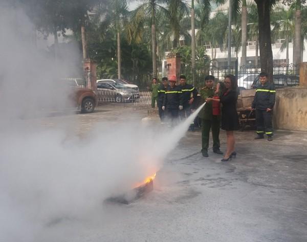 Các học viên sử dụng bình chữa cháy dập tắt khay xăng đang cháy