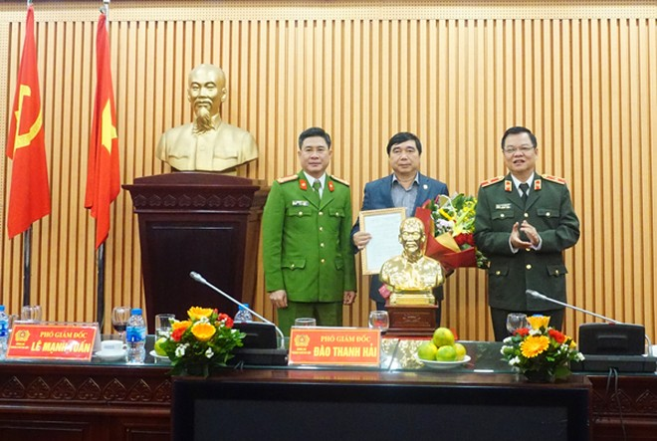Thiếu tướng Đào Thanh Hải và Đại tá Nguyễn Tuấn Anh - Phó Giám đốc CATP trao quyết định nghỉ hưu và tặng hoa chúc mừng Đại tá Lê Mạnh Tuấn