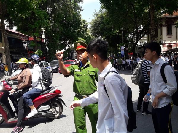Thượng úy Vũ Đức Nghĩa căng mình dưới nắng nóng phân luồng đảm bảo ATGT cho các thí sinh dự thi tại điểm trường THPT Trần Phú