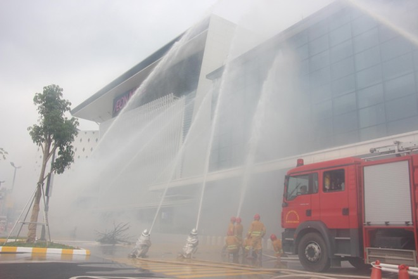 Lực lượng Cảnh sát PCCC và CNCH phối hợp với lực lượng chữa cháy cơ sở phun nước khống chế đám cháy