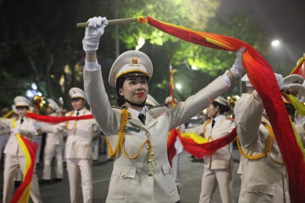 Đông đảo người dân chăm chú theo dõi những điệu múa do các nghệ sỹ Đoàn Nghi lễ CAND biểu diễn, diễu hành dọc theo tuyến phố Đinh Tiên Hoàng