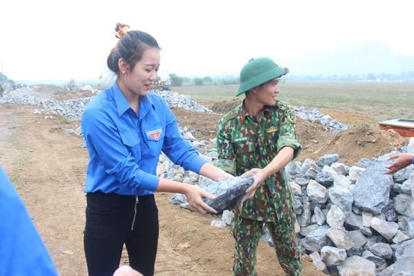 Đoàn viên thanh niên xã Trần Phú hỗ trợ các anh bộ đội chuyển đá xây tường rào bảo vệ sân bay Miếu Môn
