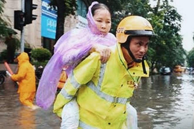 Hình ảnh chiến sỹ CSGT- CATP Hà Nội giúp người dân qua điểm ngập nước mùa mưa bão