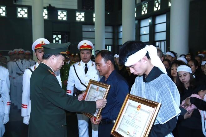 """Bộ trưởng Bộ Công an Tô Lâm trao tặng Huân chương Chiến công hạng Nhất và Bằng """"Tổ quốc ghi công"""" cho đại diện gia đình 3 đồng chí."""