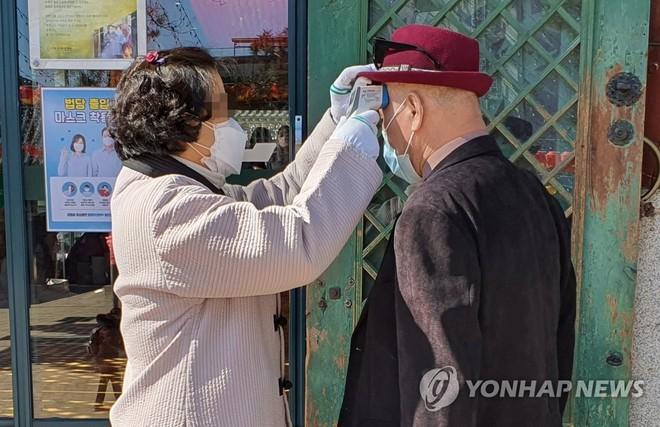 Kiểm tra thân nhiệt du khách trước cửa một ngôi đền ở Seoul