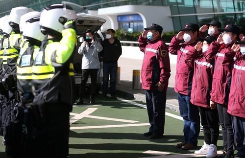 Các thành viên của đội y tế từ khu tự trị Tân Cương của Trung Quốc và cảnh sát giao thông Vũ Hán chào nhau bên ngoài sân bay quốc tế Vũ Hán trước khi bay về nhà