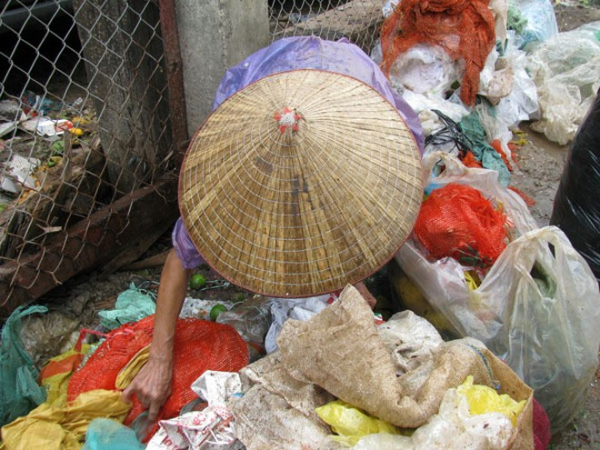 Bà Sinh vẫn mải miết phân loại rác dù trời đang mưa tầm tã.