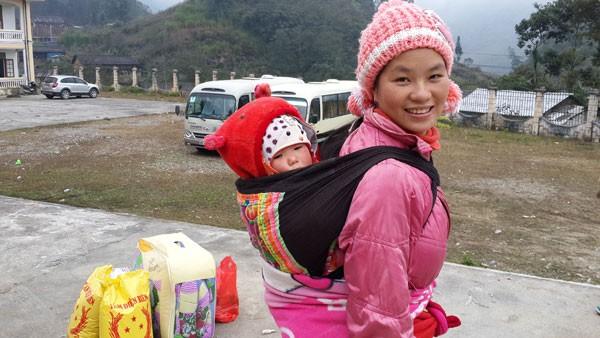 Một bà mẹ địu con đang ốm trên lưng tới nhận quà.