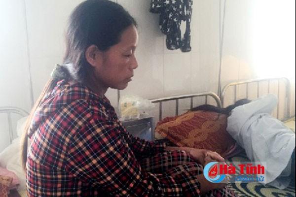 """Chị Nguyễn Thị Lý ngồi lặng bên đứa con của mình sau khi bạn học """"đánh hội đồng""""."""
