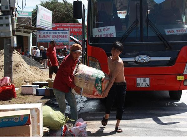 Hành khách và nhà xe đang chuyển đồ sang xe khác để tiếp tục hành trình.
