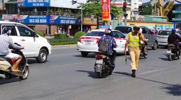 Chiến sĩ CSGT phơi mình giữa trời nắng xử lý vi phạm giao thông.