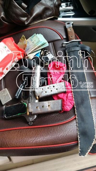 Khẩu súng đã lên đạn, hộp tiếp đạn và đao, Phong đặt cạnh ghế lái xe ô tô