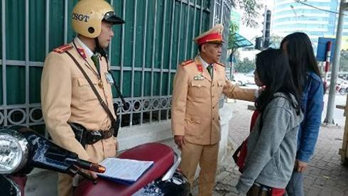 Đại tá Đào Vịnh Thắng, Trưởng Phòng CSGT nhắc nhở các em học sinh đội mũ bảo hiểm khi tham gia giao thông.
