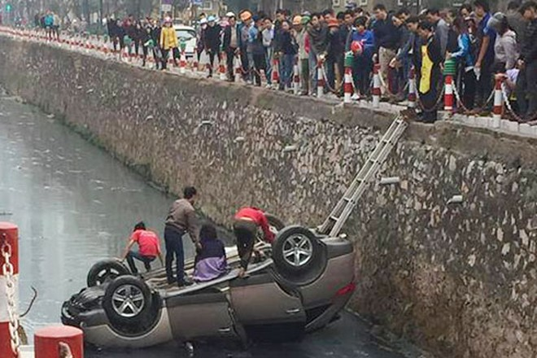 Người phụ nữ bên trong xe được người dân cạy cửa đưa ra ngoài.