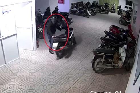 Nam thanh niên bịt khẩu trang, đội mũ bảo hiểm thản nhiên lấy trộm xe máy trong nhà đề xe chung cư (ảnh: cắt từ clip)