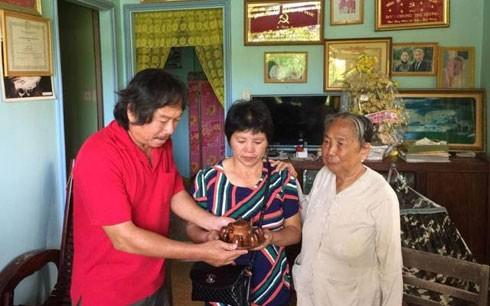 Nhà báo Nguyễn Phấn Đấu trao tặng bà Mi bộ ấm chén trước khi bà về Trung Quốc.