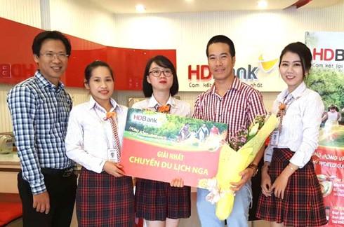 Khách hàng Bạch Minh Khoa (thứ hai từ phải sang) giao dịch tại HDBank Lê Quang Định (TP.HCM) nhận giải nhất – chuyến du lịch xem WorldCup 2018 tại Nga trị giá 50 triệu đồng.