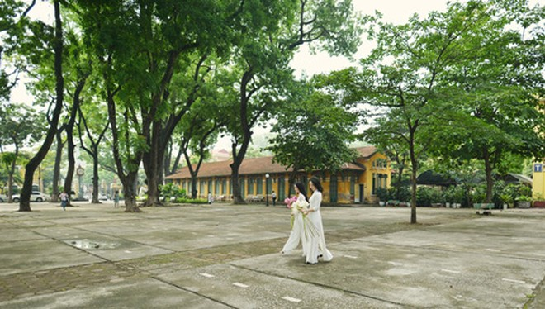 Bạn nữ trong tà áo dài trắng cùng đóa sen Tây Hồ trên sân trường.