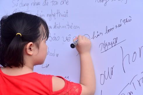 Một em bé viết thông điệp bảo vệ môi trường