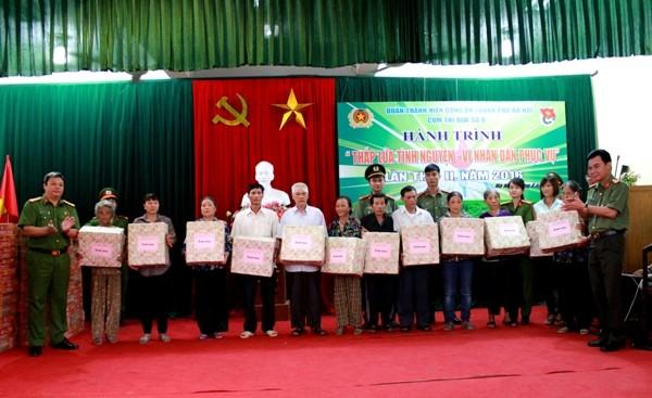 Đại tá Nguyễn Anh Tuấn, Phó Giám đốc CATP Hà Nội trao quà cho các gia đình chính sách
