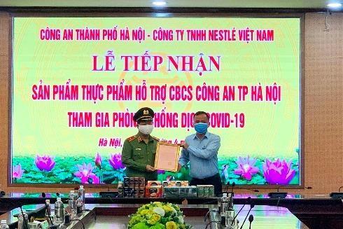 Thiếu tướng Đoàn Ngọc Hùng, Phó Giám đốc Công an thành phố Hà Nội trao thư cảm ơn của Giám đốc Công an thành phố tới đại diện Công ty TNHH Nestlé Việt Nam
