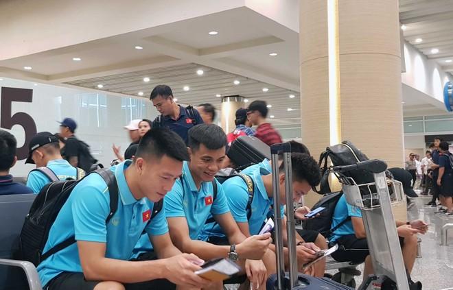 Các tuyển thủ liên lạc với người thân khi chờ lấy hành lý